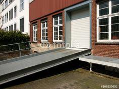 Einfahrt mit Rampe und Rolltor in ein altes Lagerhaus mit rotbrauner Backsteinfassade in Bielefeld-Schildesche