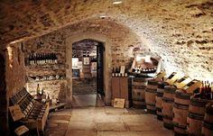 cave à vin authentique aménagée avec des étagères en verre et des barriques