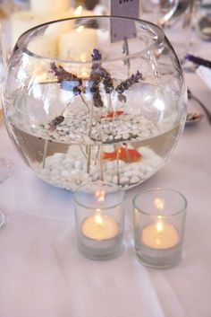 Centre de table avec un bocal et un poisson rouge pour un mariage sur le thème mer.