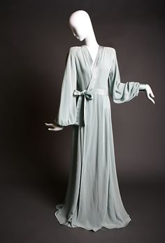 "Ossie Clark ""Cuddly"" Wrap Gown 1973 Feminine, sexy and romantic, are all characteristics of what Ossie Clark's fashionable garments were about. This beautiful example is fashioned from an exquisite shade of teal blue iridescent moss crepe- very fluid like, silky and smooth, and of the perfect weight to hang in such a sexy manner.  The gown is wrap-fronted, and ties at the side waist with a satin tie belt.  Featuring wide balloon sleeves, with fitted satin cuffs and crepe covered buttons, and…"