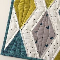 Pretty patchwork diamonds, in a striking palette of teal, chartreuse green, and gray, are set against a black-and-white polka-dot background in this small, modern quilt. Angled quilting lines accentuate the shape of each diamond, and create a beautiful stitched pattern on the quilts back. Sewn from start to finish in my studio, this mini wall hanging features prints by an all-star roster of modern fabric designers, including Bonnie Christine, Carolyn Friedlander, Denyse Schmidt, Maze and…