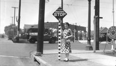 A Los Angeles stop sign in 1925, shortly after the traffic safety signs were introduced in the city. Per the recommendations of the First National Conference on Street and Highway Safety of 1924, the signs featured a diamond shape with white letters over a red background. Octogonal stop signs arrived in L.A. several years later.    Part of the USC Digital Library's Automobile Club of Southern California Collection.