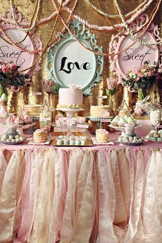 Romantic wedding dessert table with pink tulle cloth, vintage frames, and lots and lots of yummy treats