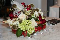 Cigar box Centerpiece with green hydrangea, ivory roses, red spray roses, peach hypericum berries, scabiosa pods, Waxflower and white ostrich plumes by Andrea Layne Floral Design (www.andrealaynefloraldesign.com)
