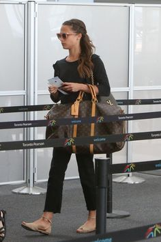 Alicia Vikander wearing Louis Vuitton Weekend Bag and Ragdoll La Ruffle Tee in Faded Black