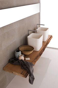 Love the mix of materials and colors. The gray tile, natural wood is great. Not crazy about the vessels and fixtures.
