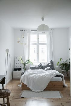 Cozy bedroom with a bed in front of the window, white walls and lots of white interior decor.