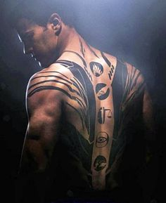 The symbols of each faction are on his back: Dauntless (The Brave) at the top of his spine, Abnegation (The Selfless) below it, the other three smaller below them (Candor - The Honest, Erudite - The Intelligent, and Amity - The Peaceful ). Oh and written on his plain white bedroom wall are the words: Fear God Alone. <3 him!!!!