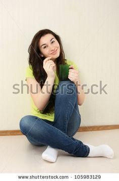 Sitting Cross-Legged | Happy casual girl sitting cross-legged with mug indoors - stock photo