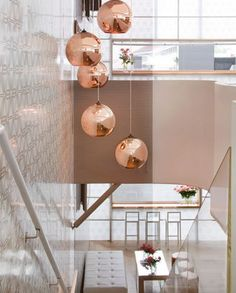Different height pendants fill the empty space within this stair well