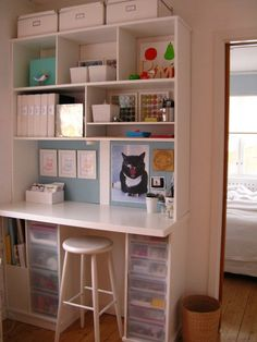 A wall of simple built-ins, along with IKEA boxes, transparent drawers and a countertop make the most of one small area of the room.