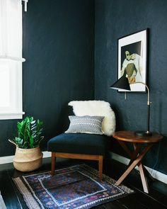 Moddy room vibes via dark green walls, wall art, belly basket and vintage rug
