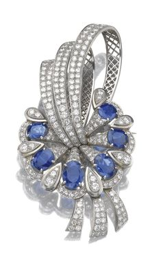 Sapphire and diamond brooch/ pendant, 1950s Of stylised foliate design, set with oval sapphires, to a mount millegrain set with circular- and single-cut diamonds, detachable brooch fitting, accompanied by fitted case signed Hamilton & Co Ltd.