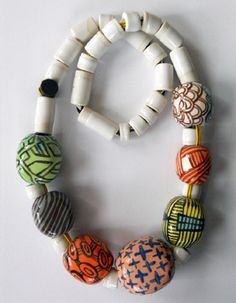 """Megan Bogonovich, Necklace in glazed ceramic with woven fiber cord. Necklace is 32"""" in length. Center bead measures 1.75 x 2 x 1.5"""""""