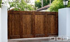 <b>Los Angeles, CA</b> - As part of a multiple phase project for this LA residence we designed and handcrafted a <b>rustic style drivewaygate</b> in simple <b>Spanish architectural style driveway gate</b>. The gate features a simple tongue and groove backdrop with horizontal and vertical trim that create a minimalistic <b>Spanish Colonial style</b>. Wire-brushing the alder wood added depth and brought out the natural grain structure. In order to accentuate and protect the wood we hand-...