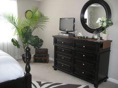 Romantic Safari bedroom    I love the dark wood furniture, rug and greenery - FK