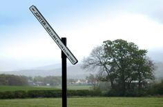 Artwork: PROPOSAL 90, A SIGNPOST TO JUPITER by Peter Liversidge.  A cast iron information sign pointing upwards at 70 degree angle with the inscription 'Jupiter - 893 million to 964 million kilometres'.  This signpost is placed along the parkland drive and is a reminder of the planet as opposed to the god Jupiter is named after.