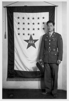 Yukiyasu Uyeoka, soldier of the United States army, stands before the Poston Relocation Center's service flag as one of the 553 boys of Japanese ancestry whose parents now reside in the relocation center. Each week the number of stars increase on the Poston Service flag, as more boys volunteer and are accepted for service.