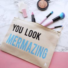 Slogan make up bag from Rock On Ruby!<strong>Colour</strong>: Make Up Bags available in black or cream <strong>Size: Small and Medium</strong><strong>A handy make up bag to help keep you looking Mermazing throughout the day!</strong> This item is a printed, natural canvas bag with official Rock On Ruby logo. The makeup bag fastens with a vintage style metal zip. With pastel printed design to give a fab, modern effect. <strong>Slogan reads: You Look Mermazing</strong> <strong>Available in…