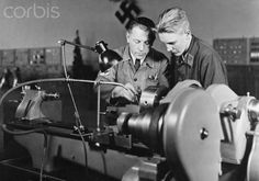 An apprentice of Ernst Heinkel Flugzeugwerke (Ernst Heinkel Aircraft Manufacturer) is pictured with a teacher during the production of aircraft parts between 1937-1943. Place unknown. The Ernst Heinkel Flugzeugwerke was one of the leading defense industry manufacturer in the Third Reich. Photo: Berliner Verlag/Archiv