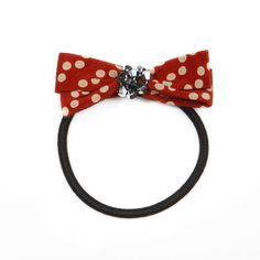 The russet red and cream polka dot Betsy bow, will anchor tumbling tresses with flair.  Find it on Splendor Designs
