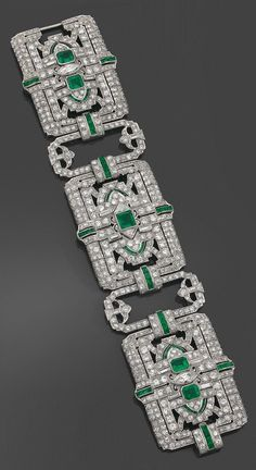 A rare and spectacular Art Deco platinum, diamond and emerald bracelet, by Yard, circa 1925. The articulated bracelet composed of three broad, openwork plaques, joined by openwork links, set with diamonds and emeralds, mounted in platinum. Signed.