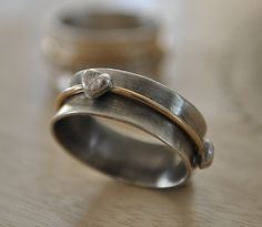 This adorable mixed metal spinner ring is handmade and features three fine silver hearts that spin on a delicate 14k gold-filled band. I have charcoal cast each heart individually from molten fine silver which is .999 % pure silver. This process gives each heart a unique character and finish. The band is made made from .9 mm thick sterling silver sheet and is 9 mm wide. I lightly oxidized the band to create contrast making the gold and gleaming fine silver hearts really pop. This ring would…