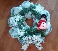 SOLD = Beautiful and fun winter wreath with a light up snowman accented with big snowflakes and a fun polka dot bow.