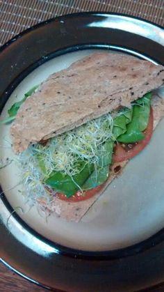 Sándwich con pan chapati, brotes de alfalfa, tomate, albahaca y rucula.