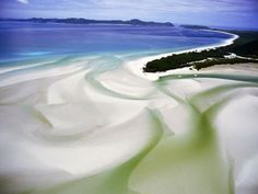 Sandbars flow into the Coral Sea at Whitsunday Island National Park in Queensland, Australia.