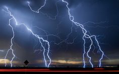 "New Mexico Lightning - Photographer wrote, ""One of the real treats of the Southwest is the thunder and lightning storms we get in the summer. The light trails are cars passing by as the shutter was open. The camera was mounted on a window mount tripod."""