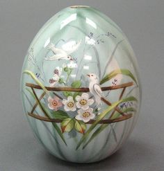 RUSSIAN PORCELAIN EASTER EGG 20th century, painted with flowers and love birds on a bluish-grey ground .