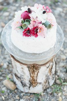 Rustic white wedding cake with real flowers on top.