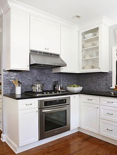 Contrast and Consistency The rich, stained wood floors add a sense of warmth and consistency to the home, as the wood floors continue on throughout the house. That, in contrast with the blue-gray tile backsplash, gives the room a balanced, put-together look. A new gas oven and cooktop replaced an electric range, giving the room a more modern feel.