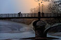 Cyclists alone on a historical bridge at dawn with lighting by lanterns.  Radfahrer allein auf historischer Brücke in Morgendämmerung mit Beleuchtung durch Laternen.