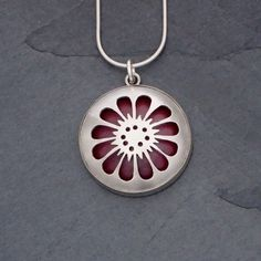 "Fire Within Pendant 6 from Sarah McCulloch Designs- The pierced sterling silver reveals a layer of vibrant, flame-patinated copper. 1.25"" in diameter and ⅜"" deep, domed by hand and set in a sterling silver bezel. Available with a 16"" or 18"" sterling silver snake chain.  1.25"" diameter, ⅜"" depth, 22 gauge sterling silver"
