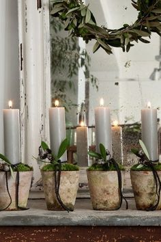 Grouping of candles in small ceramic plant potting containers.