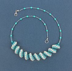 Learn how to create your sparkling Cellini Spiral Necklace with beaded chain on either side.