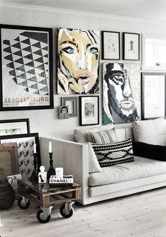 decoração sala de estar no estilo industrial com sofá claro, quadros e posters nas paredes, mesa lateral de palet com rodinahs