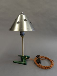 Telford Table Lamp by Tim Wells. Table lamp made from vintage, found, and recycled parts. The base is created from a lawn sprinkler, painted peacock green. Lamp includes brass plumbing fittings, new vintage-style copper cloth-colored cord, a stainless steel found shade, and a lacquered steel finial. Professionally wired, not UL-listed. An edition of 5, all different but with the same shade and similar cast iron base.