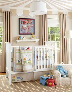 Bold circus-tent stripes on the ceiling set this nursery apart, with a polka-dot rug creating balance on the floor. The colorful animals of the crib bedding stand out against a palette of mostly tonal tans; the vivid blue of the fitted sheet is highlighted in the quilt border, the wall art and other playful decorative accessories. White furniture keeps the room feeling bright and clean.