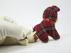 We appreciate your interest in this adorable plaid stuffed dog. In addition to being a straw-stuffed pincushion, his little tail extends to reveal a