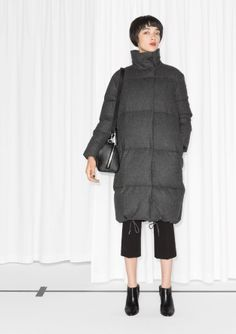 An oversized quilted coat featuring an understated and timeless urban-chic style.