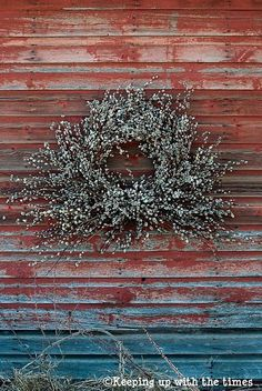 This simple pussy-willow wreath contrasts so well with the wood it is mounted on and costs... pinned with Pinvolve