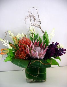 Tropical arrangement with king protea, pin cusion protea, stock green leaves