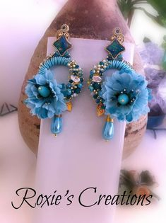 Colorful turquoise circle earrings with large colored textile flowers and embroidered with crystals, river pearls and strass chain. The earrings are pin-fastened behind the lobe and are very light. Perfect for summer and tanning, they can be worn from morning to night because they