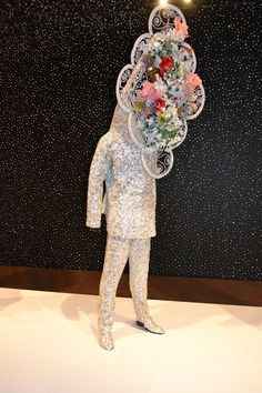 """One of Nick Cave's soundsuits (pictured) features a vintage funeral wreath in place of a face.    Cave grew up with seven siblings in Columbia, Mo. and has credited his single mother with encouraging his creativity. """"Growing up, I would get hand-me-downs and always felt the need to change them,"""" said Cave."""