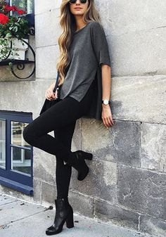 Woman in a dark grey side-slit loose t-shirt, black pants and boots