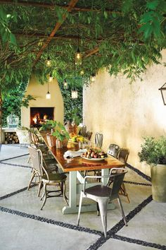 Now It's an Outdoor Dining Room - Before and After Yard Makeovers That Will Make Your Jaw Drop - Southernliving. A beautiful fireplace, iron pergola draped in wisteria, and twinkling pendant lights act as the foundation of this outdoor dining room. A beautiful, long dining table with mismatched metal chairs completes the space.
