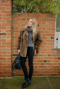 Fashion Me Now's Lucy Williams wears a slouchy gray turtleneck, black jeans, a faux fur jacket with chelsea boots // How To Dress Like A British Girl In 9 Easy Steps